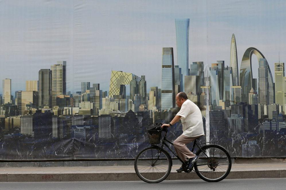 Un ciudadano pasea en bicicleta frente al cartel de un proyecto...