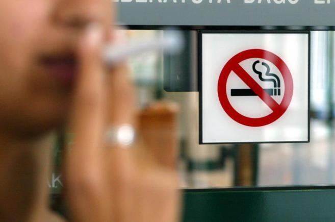 Una persona fuma junto a un comercio