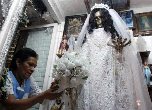 Una mujer adorna un altar a 'La Santa Muerte' en un barrio...