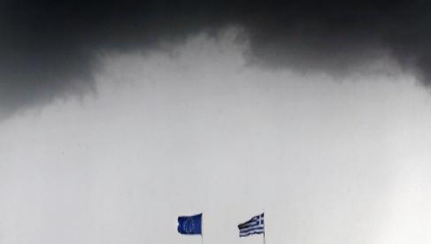 Las banderas griega y de la UE, en Atenas bajo un cielo tormentoso.