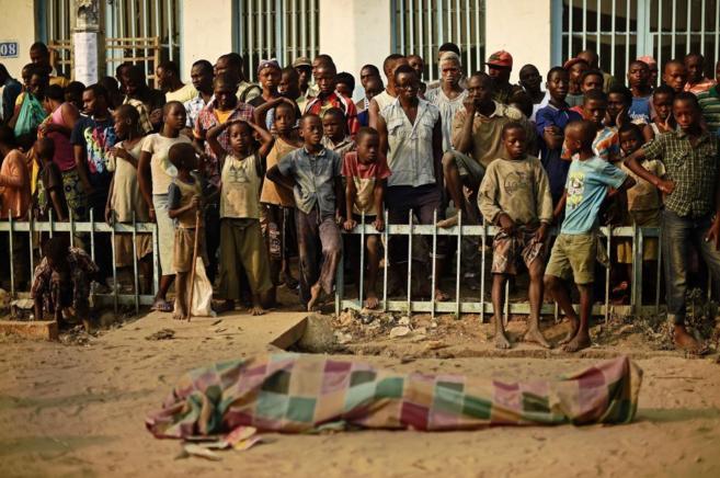 Un grupo de burundeses mira el cadáver de un manifestante muerto por...