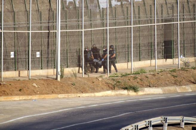Guardias Civiles se llevan a un inmigrante que estaba en la valla de...
