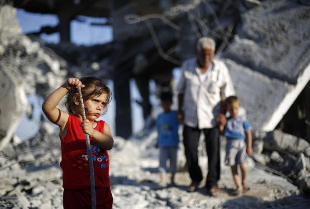 Una niña palestina juega entre los escombros de edificios destruidos...
