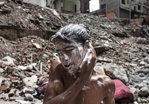 Un joven nepalí se lava la cabeza en las ruinas de Katmandú.