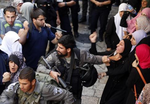Un agente  forcejea con una mujer palestina en los disturbios en...