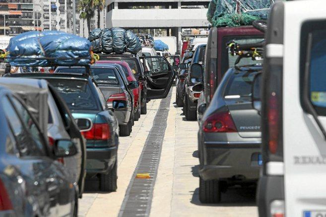 Numerosos coches hacen cola para embarcar en un ferry que los lleve al...