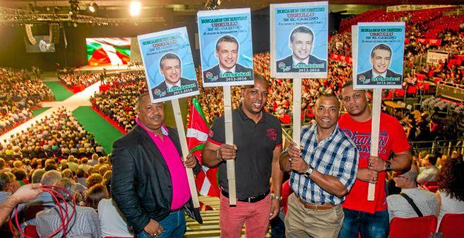 Cuatro ciudadanos extranjeros muestran carteles con la imagen de...