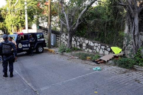 Policías junto al cuerpo de una mujer asesinada a tiros en una...