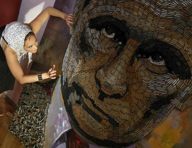 Una artista trabaja en un retrato de Vladimir Putin.
