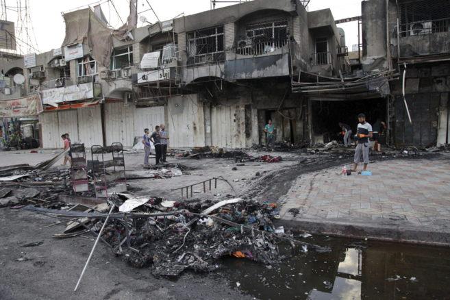 Varios iraquíes inspeccionan el lugar donde explotó un coche bomba...