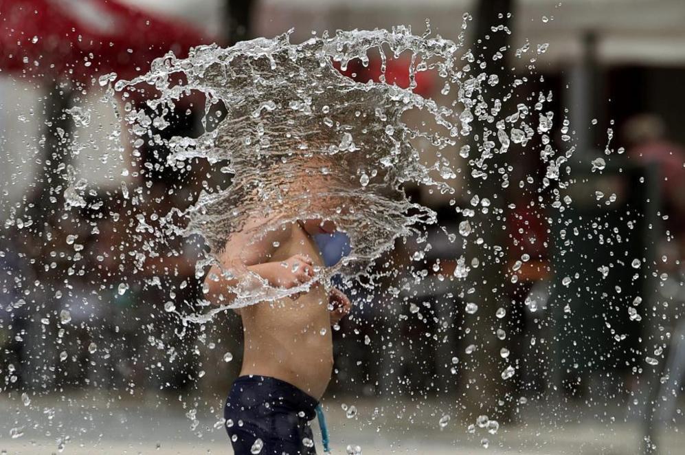 Un niño se refresca en Pamplona.