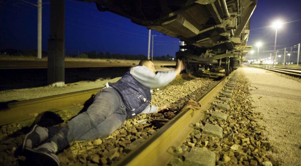 Un hombre pasa por debajo de un tren antes de llegar a la via del...