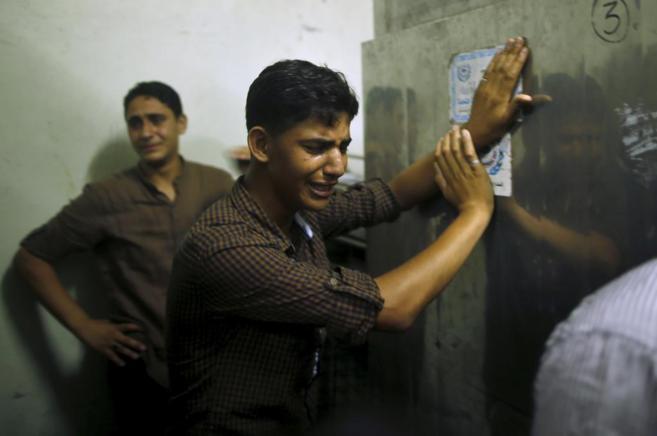Amigos de joven fallecido, Mohamed al Masri, en la morgue de Gaza.