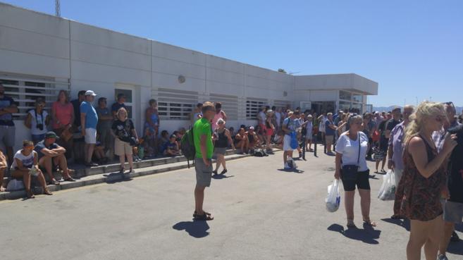 Numerosos turistas esperan al sol mientras el autobús pasa el control...