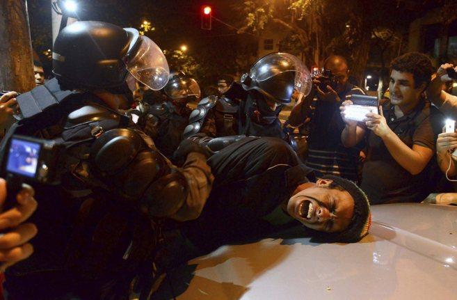 Un policía detiene a un hombre durante protestas en las calles de...