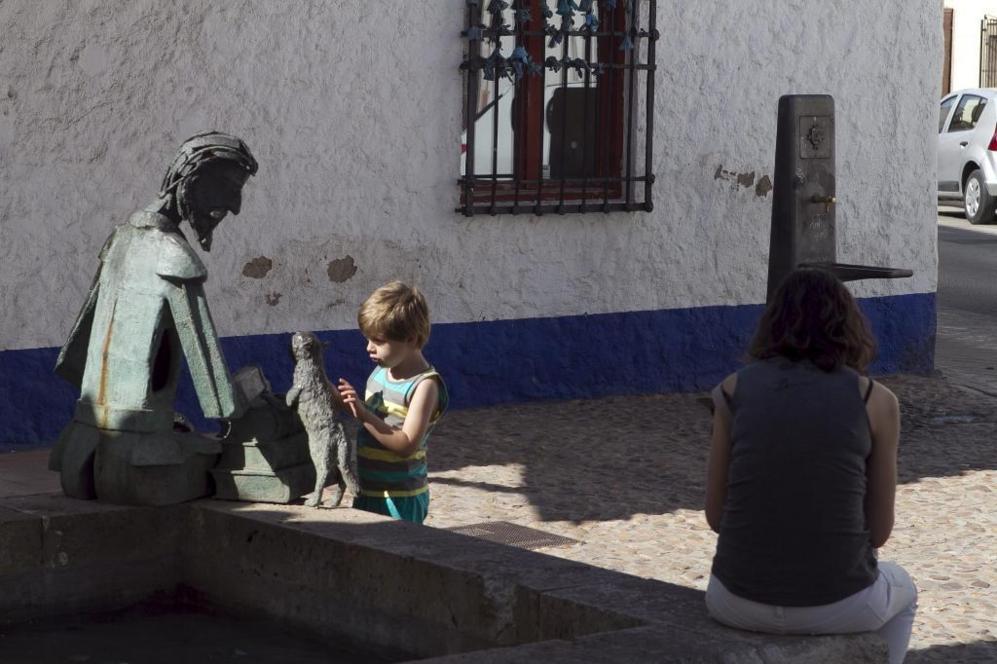 Un niño juega con la estatua de don Quijote que guarda la entrada del...