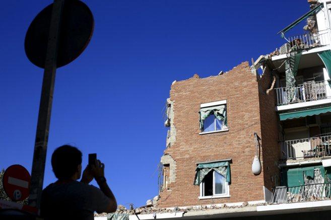 Un vecino fotografía el edificio que se derrumbó el lunes por la...
