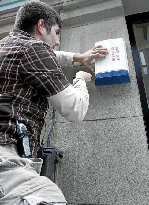 Un técnico instala una alarma en el interior de una vivienda