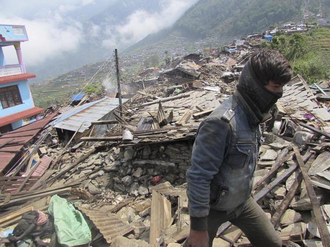 Un chico pasea entre los escombros de las casa de Barpak, al norte de...