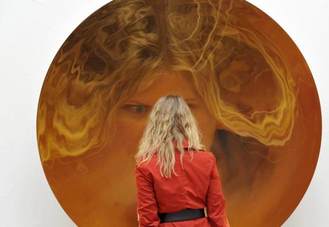Una chica se mira en un espejo cóncavo