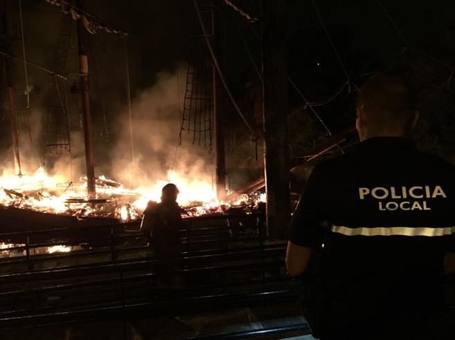 Policías locales y bomberos durante la extinción de las llamas en...