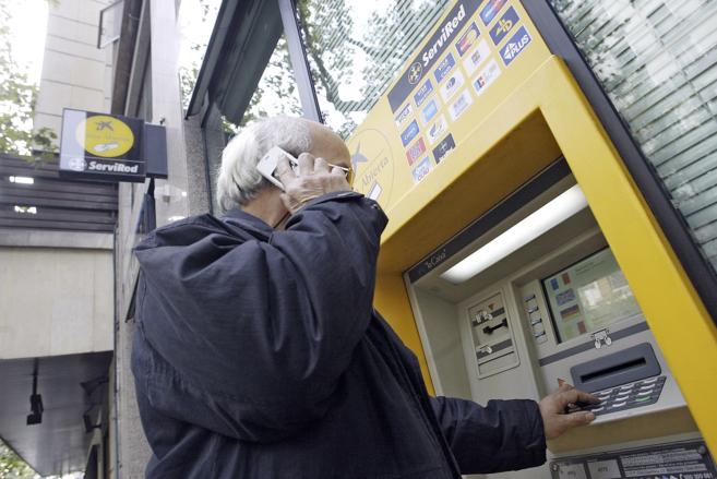 Un anciano sacando dinero de un cajero.