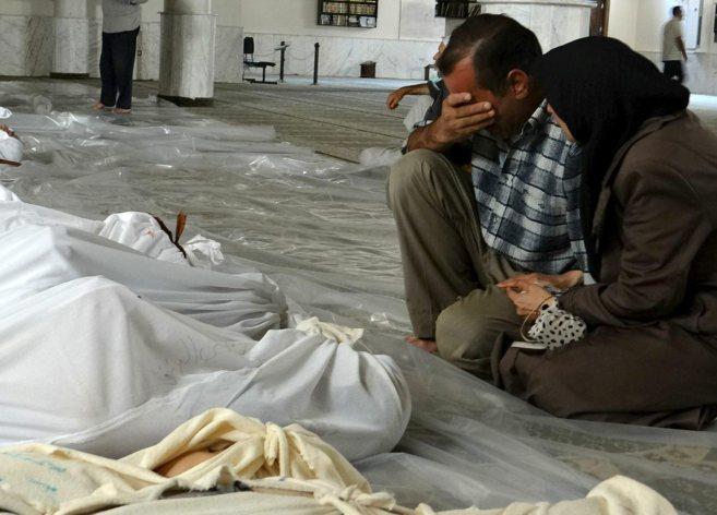 Una pareja llora enfrente de varias víctimas de un ataque químico en...