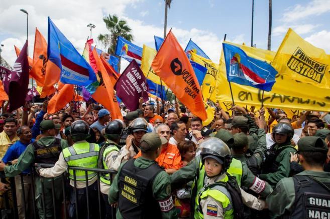 Un grupo de personas acompañan a opositores de la MUD a inscribirse...
