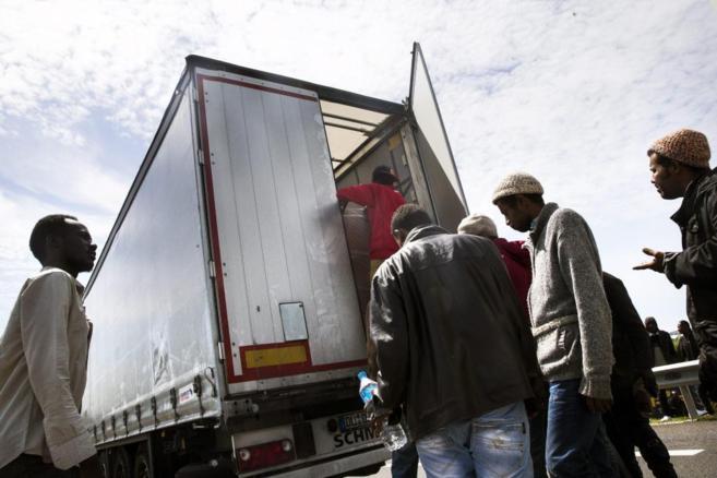 Migrantes suben a un camión para acceder al túnel del Canal de la...