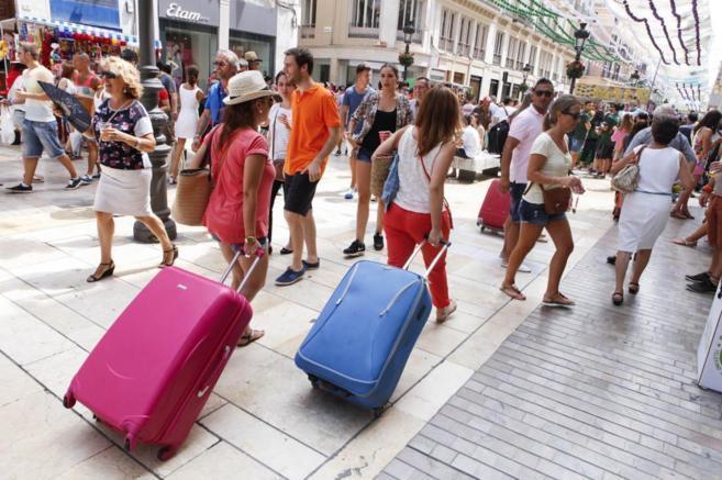 Varias personas caminan por una calle comercial