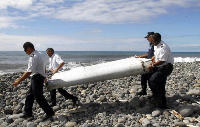 Miembros de la gendarmería francesa transportan un resto de un avión...