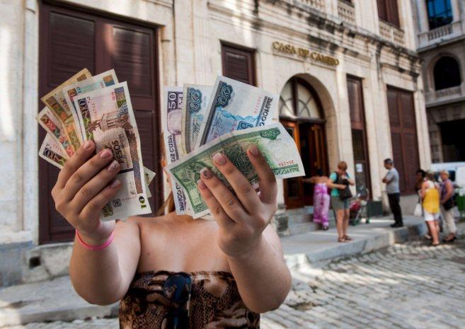 Una mujer con pesos cubanos (en la mano izquierda) y convertibles (en...
