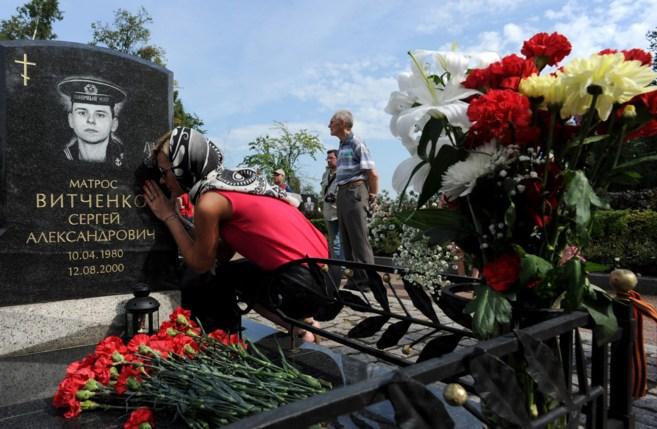 Una mujer reza junto a la tumba de uno de los marineros que murieron...