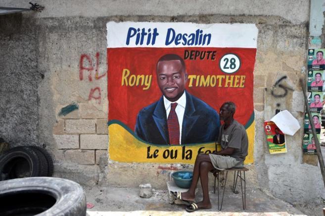 Un hombre sentado junto a un cartel electoral, en Puerto Príncipe, el...