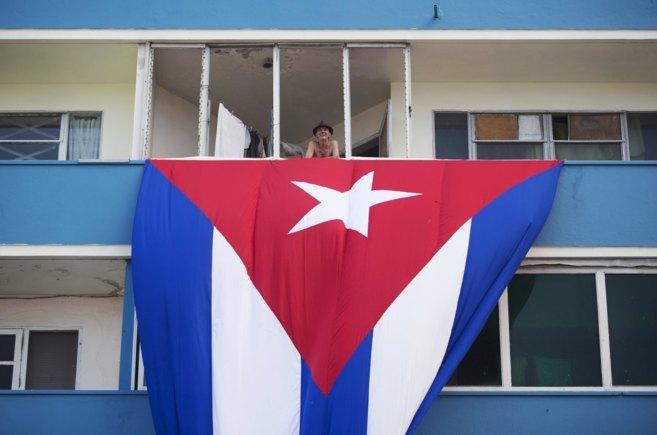 Un cubano, en la terraza de su vivienda donde cuelga la bandera...
