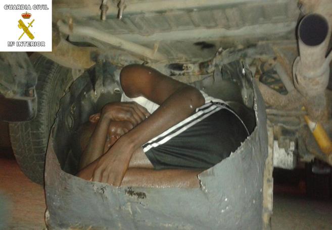 Momento del rescate del inmigrante escondido en el hueco de la rueda...