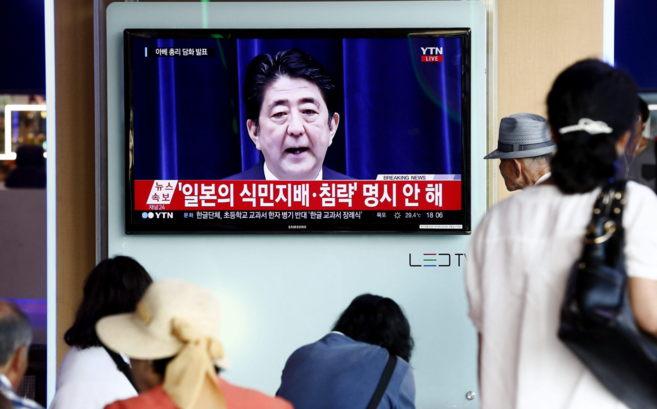 Ciudadanos de Corea del Sur atienden el discurso de Abe desde Seúl,...