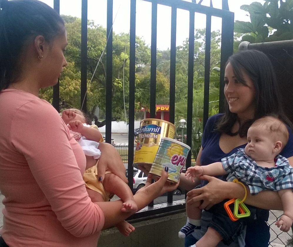 La periodista (dcha.) intercambiando leche infantil para bebés...