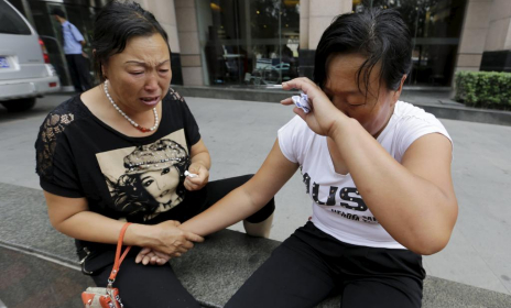 Dos familiares de un bombero desaparecido lloran en Tianjin
