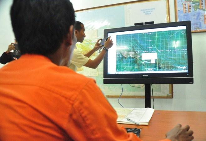 Miembros de los equipos de rescate observan un mapa de la zona donde...
