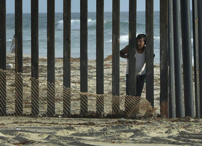 Un inmigrante se asoma por una valla fronteriza entre México y...
