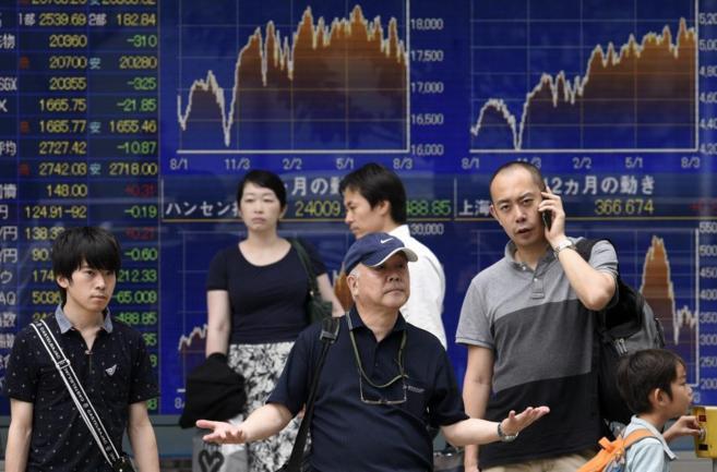 Varias personas con los gráficos de la Bolsa de Tokio de fondo