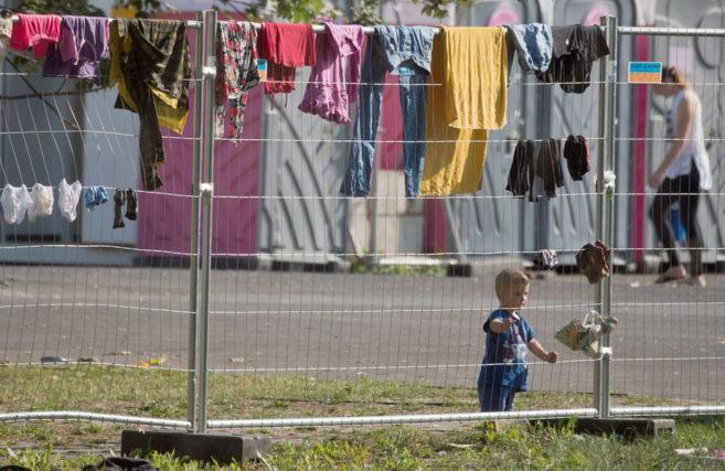 Un niño, junto a una valla del centro de recepción de refugiados de...
