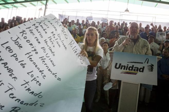 Lilian Tintori, esposa de Leopoldo López, sostiene un cartel con...