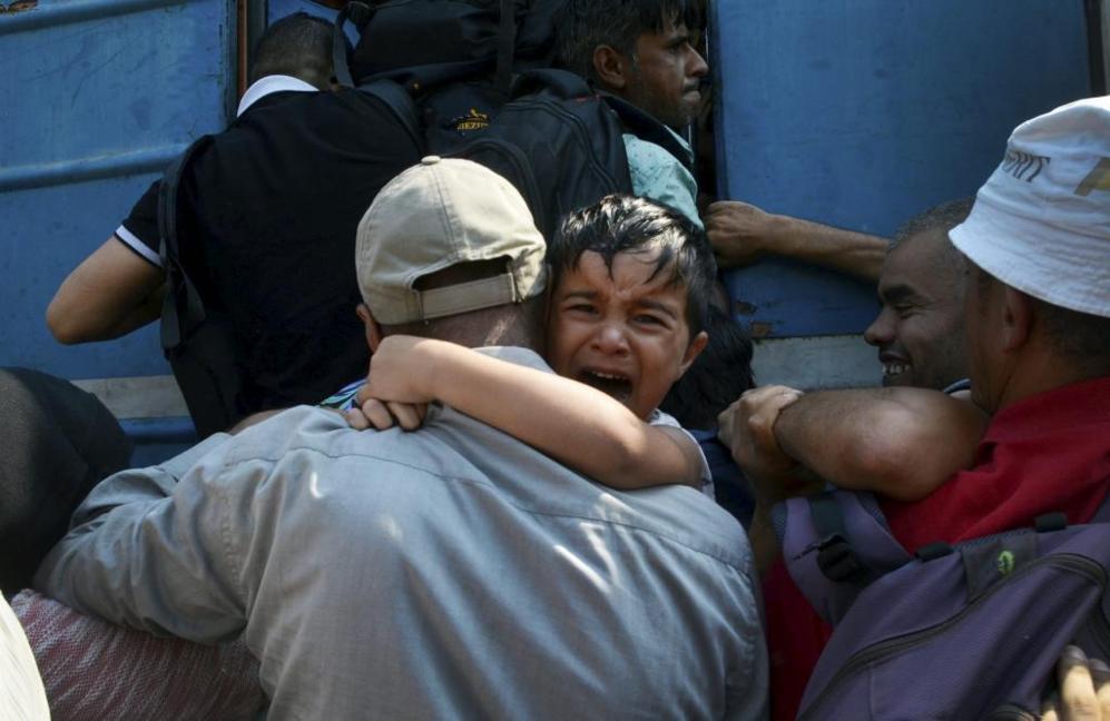 Un niño llora en los brazos de un hombre que le intenta subir al...