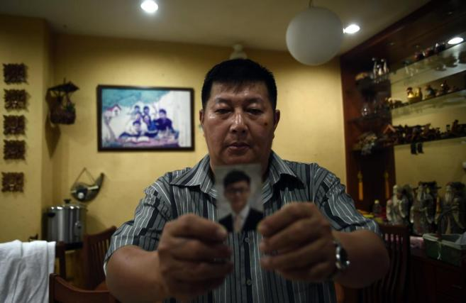 El superviviente del clan Hock Guan, Neoh, muestra la foto de su hijo,...