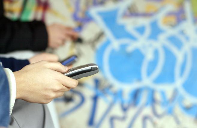 Unos jóvenes mandan mensajes por sus teléfonos móviles.