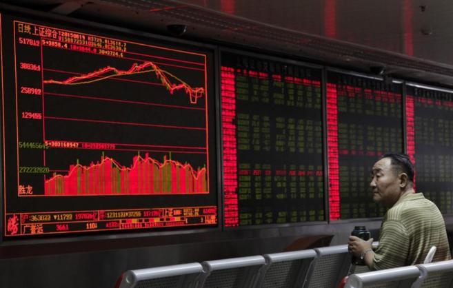 Un inversor chino sentado ante una pantalla de información bursátil...