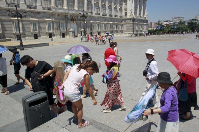 Turistas asiáticos protegiéndose del sol en el Palacio Real