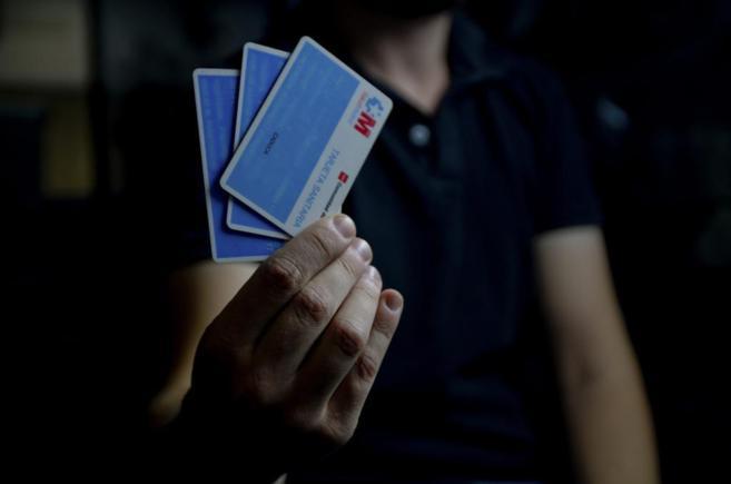 Un hombre sostiene varias tarjetas sanitarias de la Comunidad de...